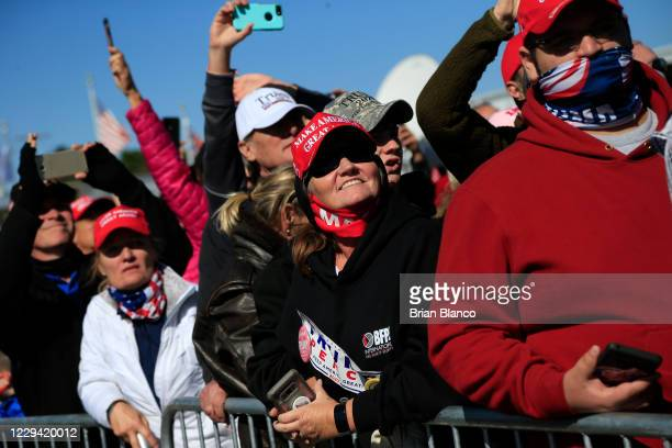 Attendees look on as U.S. President Donald Trump delivers remarks during a campaign rally at Fayetteville Regional Airport on November 2, 2020 in...