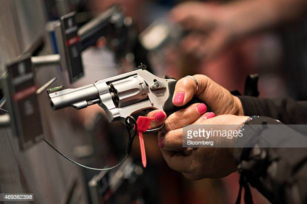 Attendees look over hand guns in the Smith Wesson booth on the exhibition floor of the 144th National Rifle Association Annual Meetings and Exhibits...