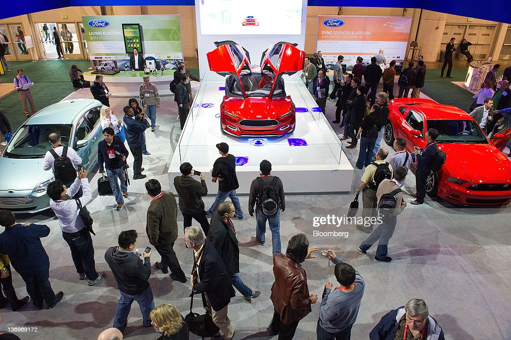 Attendees look over new Ford Motor Co. cars at the International Consumer Electronics Show (CES) in Las Vegas, Nevada, U.S., on Friday, Jan. 13, 2012. The 2012 CES trade show, which runs through Jan 13, features more than 2,700 global technology companies presenting consumer tech products and is expected to draw over 140,000 attendees. Photographer: David Paul Morris/Bloomberg via Getty Images