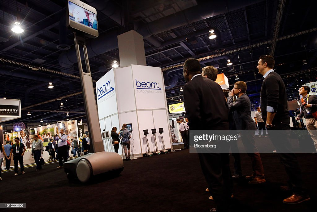Attendees look up at a large scale Beam+, a remote presence system manufactured by Suitable Technologies Inc., during the 2015 Consumer Electronics Show (CES) in Las Vegas, Nevada, U.S., on Thursday, Jan. 8, 2015. This year's CES will be packed with a wide array of gadgets such as drones, connected cars, a range of smart home technology designed to make everyday life more convenient and quantum dot televisions, which promise better color and lower electricity use in giant screens. Photographer: Patrick T. Fallon/Bloomberg via Getty Images