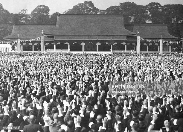 Attendees make banzai cheers during the 2600th anniversary of the National Foundation ceremony at the Imperial Palace on November 10 1940 in Tokyo...