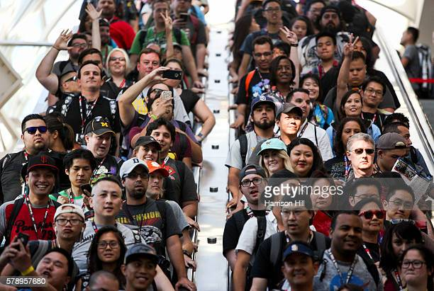 Attendees make their way towards the Exhibition hall for preview night during the first day of the Comic Con international convention at the San...