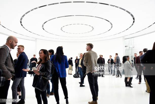Attendees mingle following an Apple product launch event at the Steve Jobs Theater at Apple Park on March 25 2019 in Cupertino California Apple Inc...