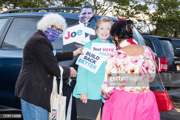 Attendees of a drive-in watch party for the Democratic National Convention hosted by the Massachusetts Democrats arrange cardboard cutouts of former...