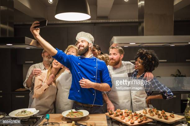 Attendees of cooking class taking selfies with Chef