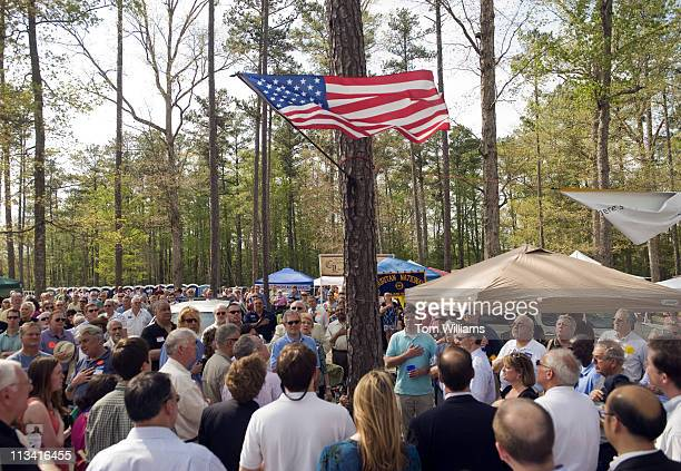 Attendees of the 63rd Annual Shad Planking political rally in Wakefield, Va., turn towards the American Flag during the playing of the National...