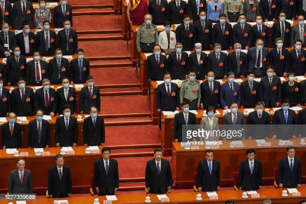 Attendees of the closing session of the Chinese People's Political Consultative Conference stand and sing the national anthem while wearing face...