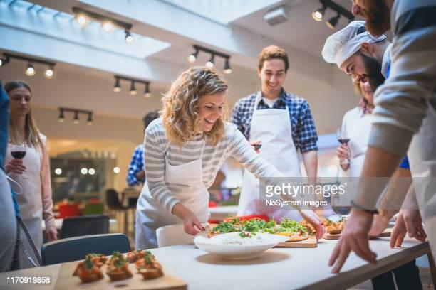die teilnehmer des kochkurses servieren ihre zubereiteten speisen für chefkoch - live ereignis stock-fotos und bilder