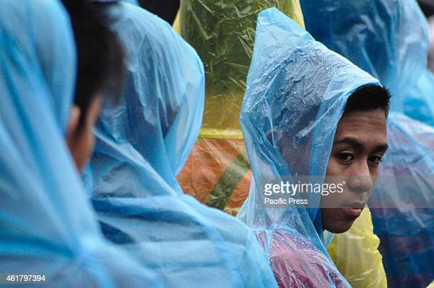 Attendees of the 'Encounter with Youth' wear raincoats after a light rain falls during the event at the University of Santo Tomas in Manila on Sunday