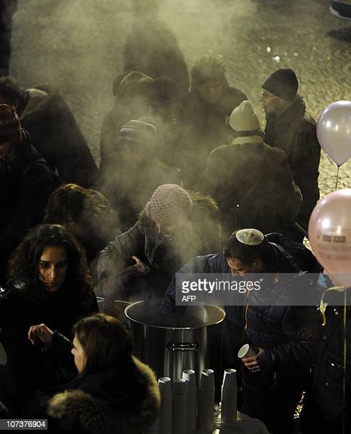 Attendees of the Festival of Lights eat soup at Dam Square in Amsterdam after a rabbi lit the candles of a sevenbranched candelabrum a menorah on...
