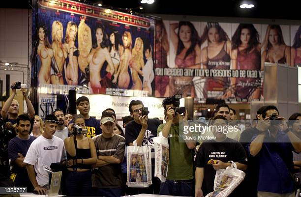 Attendees of the fifth annual Erotica LA adult entertainment trade show take photographs of the exotic dancers July 14 2001 in Los Angeles CA The...
