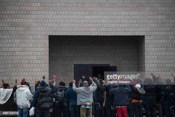 Attendees of the funeral service of Jamar Clark hold up their arms attempting to block photography of the casket as it exits the Shiloh Temple on...