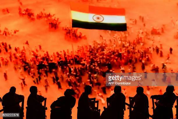 Attendees of the inaugural event of the Dr BR Ambedkar International Conference 2017 are silhouetted as an audiovisual plays in the background in...