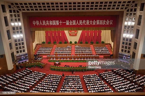 Attendees of the National People's Congress listen to Wen Jiabao China's prime minister speak during the opening at the Great Hall of the People in...