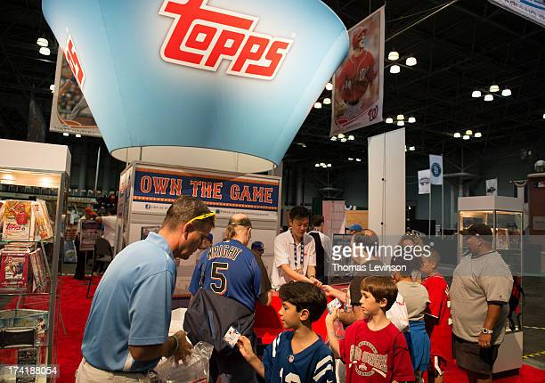 Attendees open packs of trading cards at the Topps booth during the Opening Day of TMobile AllStar FanFest at the Jacob K Javits Convention Center on...