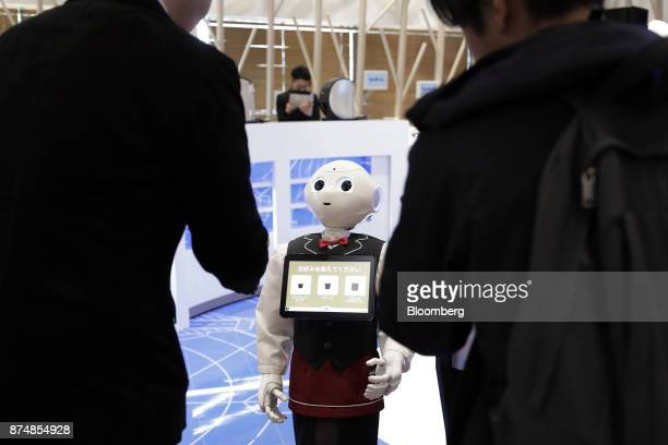 Attendees order coffee via the touch screen on a SoftBank Group Corp Pepper humanoid robot during a media preview of the humanless cafe inside Nestle...