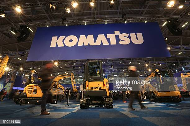 Attendees pass construction machinery on Komatsu Ltd exhibition stand during the Bauma construction industry fair in Munich Germany on Monday April...