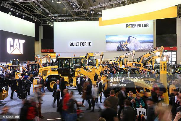 Attendees pass construction vehicles on the Caterpillar Inc exhibition stand during the Bauma construction industry fair in Munich Germany on Monday...