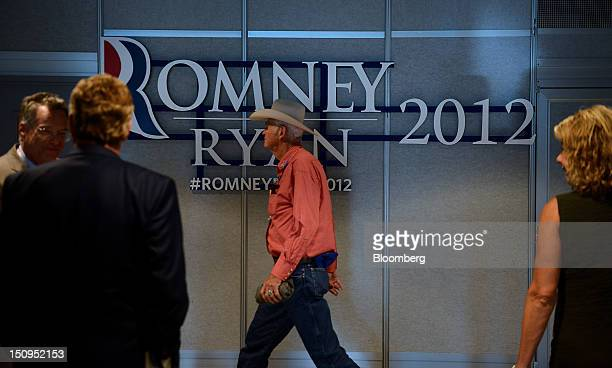 Attendees pass in front of a Romney-Ryan 2012 sign at the Republican National Convention in Tampa, Florida, U.S., on Wednesday, Aug. 29, 2012....