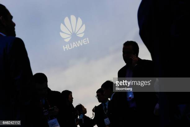 Attendees pass the Huawei Technologies Co Ltd. Stand on the second day of Mobile World Congress in Barcelona, Spain, on Tuesday, Feb. 28, 2017. A...