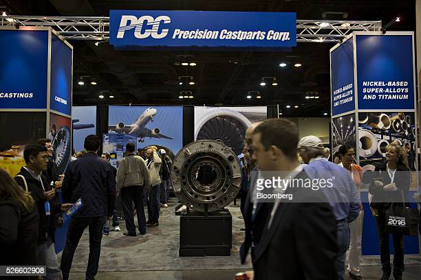 Attendees pass the Precision Castparts Corp booth during the Berkshire Hathaway Inc annual shareholders meeting in Omaha Nebraska US on Saturday...