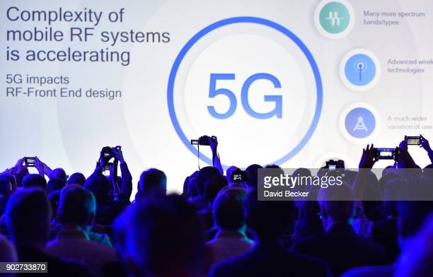 Attendees photograph a 5G logo displayed during a Qualcomm press event for CES 2018 at the Mandalay Bay Convention Center on January 8 2018 in Las...