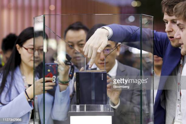 Attendees photograph a Mate X foldable 5G mobile device on display behind protective glass at the Huawei Technologies Co pavilion on the opening day...