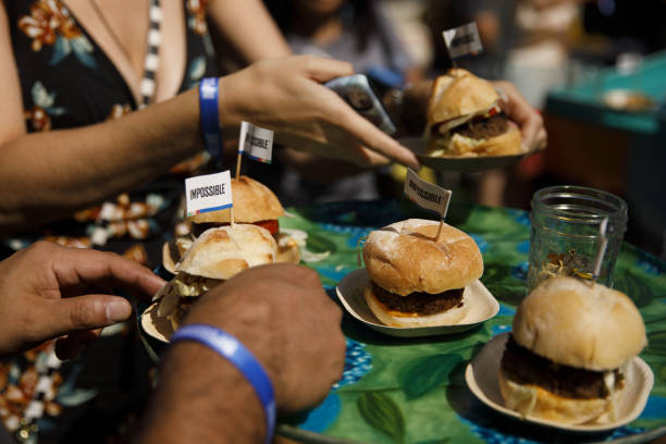 Attendees pick up Impossible Burgers during the Impossible Foods Inc. Grocery store product launch in Los Angeles, California, U.S., on Friday, Sept....