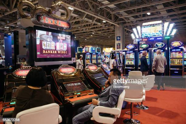 Attendees play a baccarat gaming machine at the Global Gaming Expo inside the Venetian Macau resort and casino operated by Sands China Ltd a unit of...