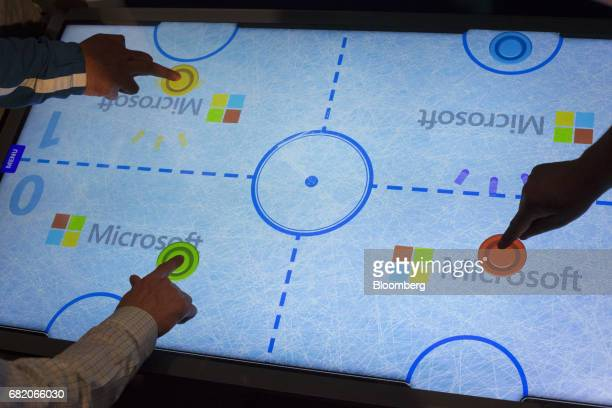 Attendees play a virtual hockey game at the Internet of Things booth on the expo floor during the Microsoft Developers Build Conference in Seattle...