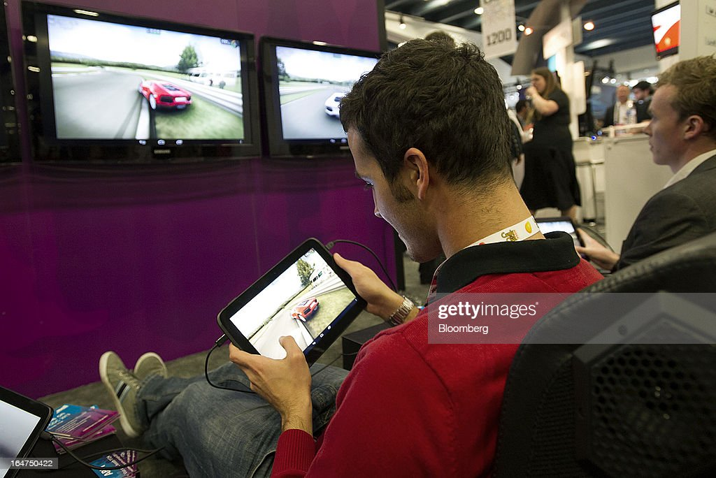 Attendees play Fishlabs VW Challenge at the Arm Holdings Plc booth at the Game Developers Conference 2013 in San Francisco, California, U.S., on Wednesday, March 27, 2013. With over 22,500 attendees, the Game Developers Conference is the world's largest and longest-running professionals-only game industry event. Photographer: David Paul Morris/Bloomberg via Getty Images