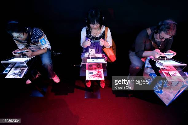Attendees play games on Sony Computer Entertainment Inc's PlayStation Vita handheld game consoles during the Tokyo Game Show 2012 at Makuhari Messe...