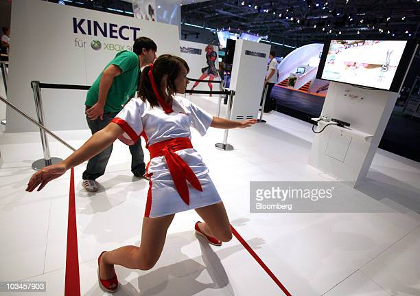 Attendees play the 'Cross Board' video game using the motionsensing 'Kinect' accessory on a Microsoft Corp Xbox 360 gaming console at the Gamescom...