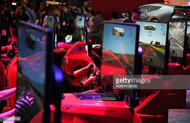 Attendees play the Gran Turismo 6 driving video game for Playstation 3 on the first day of the Electronic Entertainment Expo in Los Angeles on June...