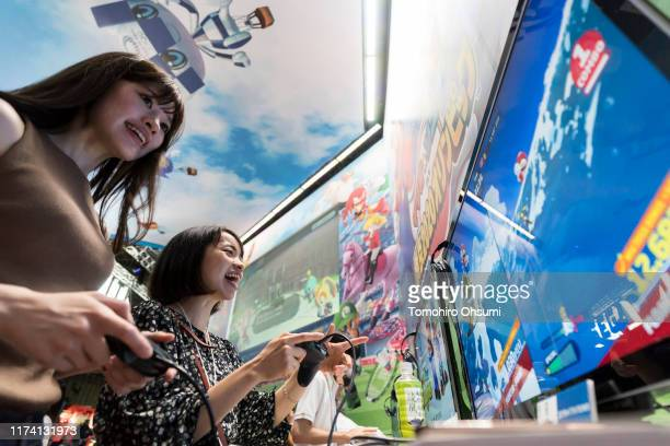 Attendees play the Mario & Sonic Olympic Games Tokyo 2020 video game in the Sega Games Co. Booth on the business day of the Tokyo Game Show 2019 at...
