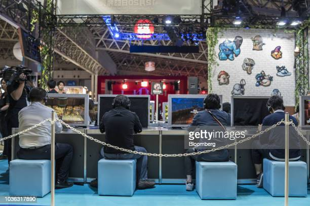 An attendee wears a virtual reality headset to play a motorcycle video game at the JPPVR booth during a media preview day of the Tokyo Game Show in...
