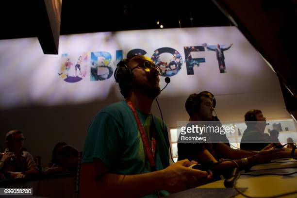 Attendees play the Ubisoft Entertainment SA 'Assassins Creed Origins' video game during the E3 Electronic Entertainment Expo in Los Angeles...