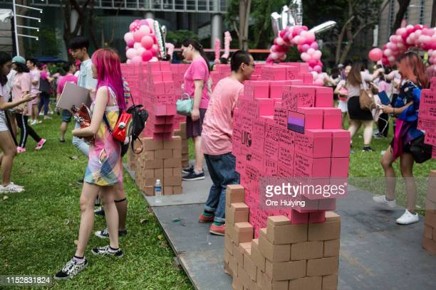 Attendees pose for a photo at the message of hope board during the Pink Dot event held at the Speaker's Corner in Hong Lim Park on June 29 2019 in...