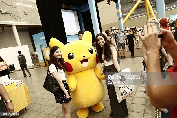 Attendees pose for a photo with a life size Pikachu character from the anime and game series 'Pokemon' at Hyper Japan the UK's biggest Japanese...