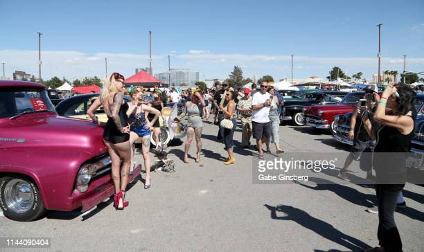 Attendees pose next to custom vehicles for photos during the Viva Las Vegas Rockabilly Weekend's car show at the Orleans Arena on April 20 2019 in...