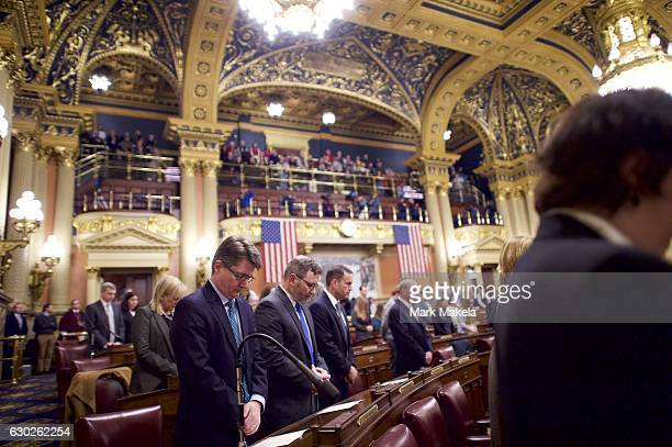 Attendees pray before electors cast their votes in the House of Representatives chamber of the Pennsylvania Capitol Building December 19 2016 in...