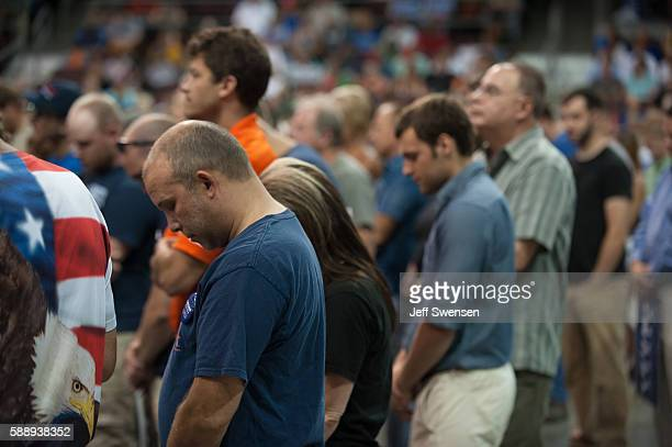 Attendees pray before Republican candidate for President Donald Trump speaks at a rally at Erie Insurance Arena on August 12, 2016 in Erie,...