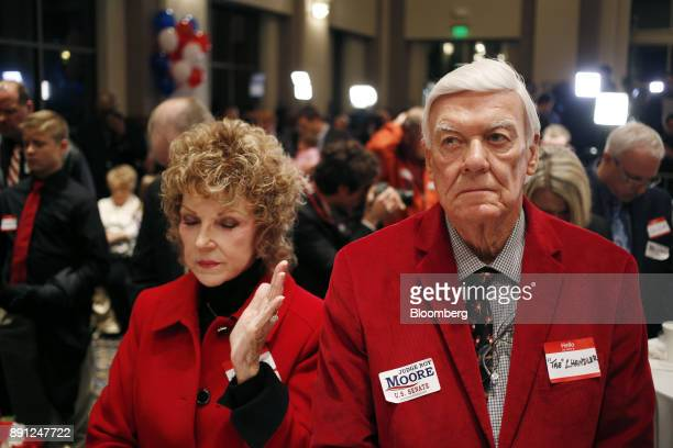 Attendees pray during an election night party for Roy Moore Republican candidate for US Senate from Alabama in Montgomery Alabama US on Tuesday Dec...