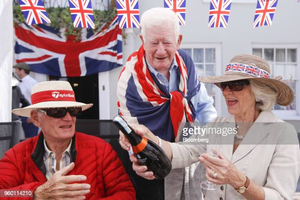 Attendees prepare to open a bottle of sparkling wine as they sit under Union flag also known as Union Jacks bunting during a street party to...