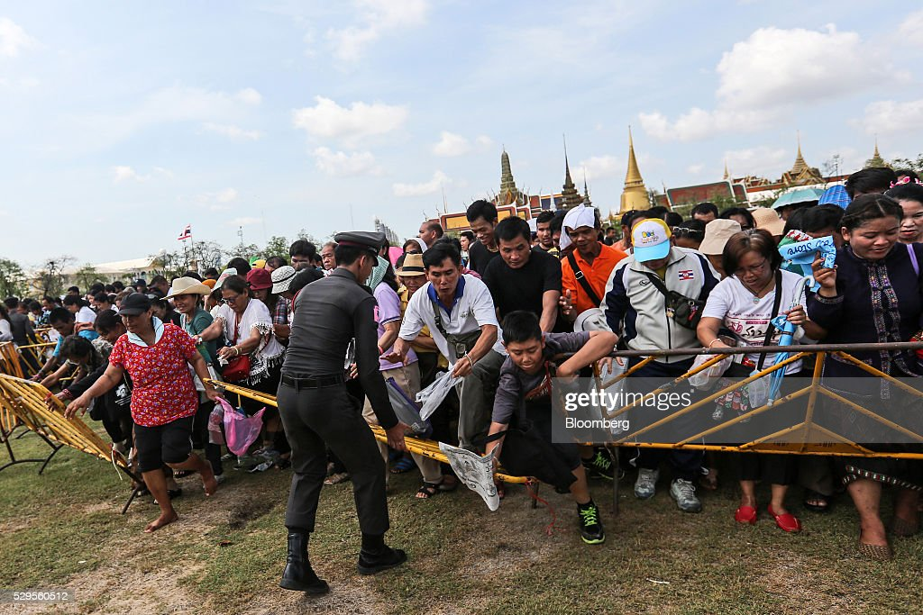 Attendees push through barriers in order to collect 'sacred' rice grains from the ground after the Royal Ploughing Ceremony at Sanam Luang park in Bangkok, Thailand, on Monday, May 9, 2016. This year may be a better one for Thai rice production. At least, that's what two sacred oxen and a ceremonial lord forecast at an annual ploughing ceremony. Photographer: Dario Pignatelli/Bloomberg via Getty Images