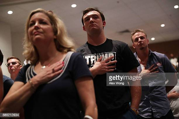 Attendees put their hands over their hearts as they listen to the national anthem during a campaign event of Republican presidential nominee Donald...