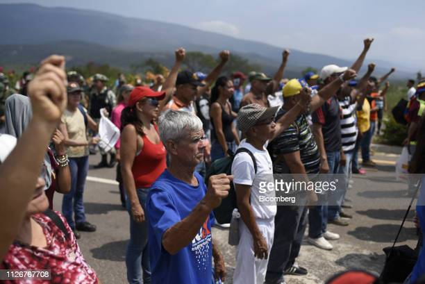 Attendees raise their fists while gathering during the Hands Off Venezuela concert at the Tienditas International Bridge in Tienditas Tachria state...