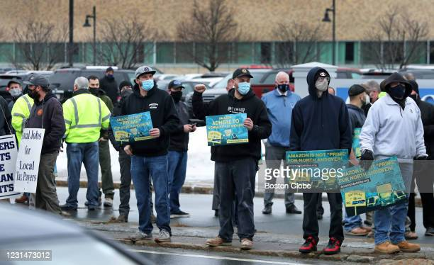 """Attendees react as a motorist goes by and blows the horn at them in support during a """"socially- distanced, outdoor rally against the controversial..."""