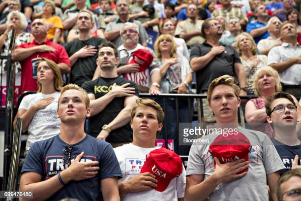 Attendees recite the Pledge of Allegiance before the start of a rally with US President Donald Trump in Cedar Rapids Iowa US on Wednesday June 21...