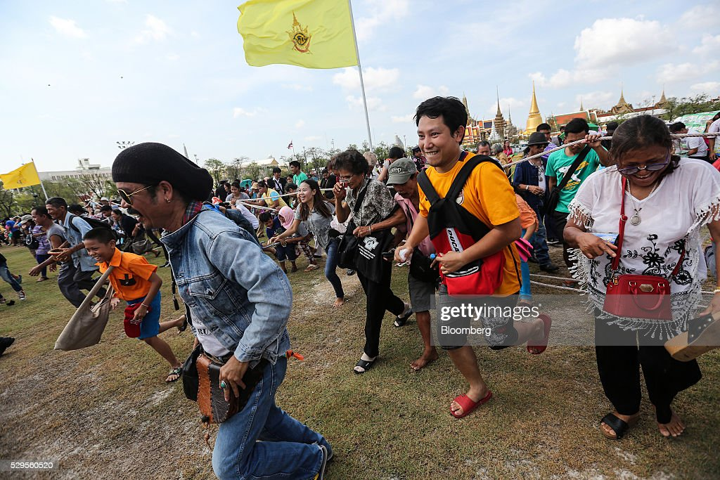 Attendees run to collect 'sacred' rice grains from the ground after the Royal Ploughing Ceremony at Sanam Luang park in Bangkok, Thailand, on Monday, May 9, 2016. This year may be a better one for Thai rice production. At least, that's what two sacred oxen and a ceremonial lord forecast at an annual ploughing ceremony. Photographer: Dario Pignatelli/Bloomberg via Getty Images